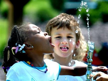 Children drinking water from an outdoor drinking fountain
